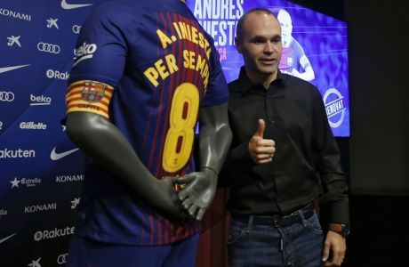 """FC Barcelona's Andres Iniesta gives the thumb up next to a shirt reading in Catalan: """"Andres Iniesta forever"""" at the Camp Nou stadium in Barcelona, Spain, Friday, Oct. 6, 2017. Barcelona has extended Andres Iniesta's contract """"for life."""" (AP Photo/Manu Fernandez)"""