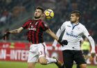 AC Milan's Patrick Cutrone, left, challenges for the ball with Atalanta's Rafael Toloi during the Serie A soccer match between AC Milan and Atalanta at the San Siro stadium in Milan, Italy, Saturday, Dec. 23, 2017. (AP Photo/Antonio Calanni)