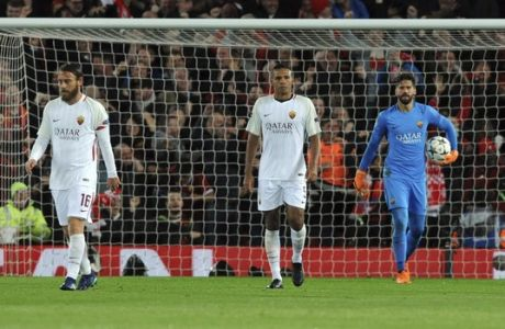 Roma goalkeeper Alisson Becker, right, Juan Jesus, center, and Daniele De Rossi react after Liverpool's Sadio Mane scoring his side's third goal during the Champions League semifinal, first leg, soccer match between Liverpool and Roma at Anfield Stadium, Liverpool, England, Tuesday, April 24, 2018. (AP Photo/Rui Vieira)