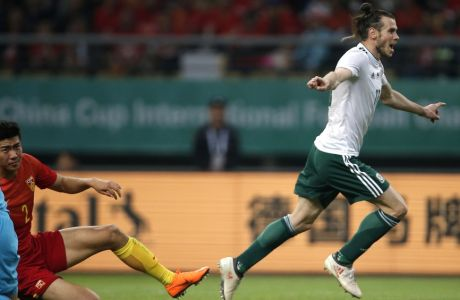 Wales' Gareth Bale,  celebrates after a goal past China's Liu Yiming, in red at the 2018 China Cup International Football Championship in Nanning in China's Guangxi province on Thursday, March 22, 2018. Wales defeated China in 6-0. (Color China Photo via AP) CHINA OUT