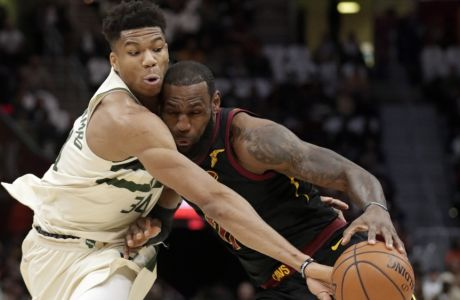 Milwaukee Bucks' Giannis Antetokounmpo, left, from Greece, knocks the ball loose from Cleveland Cavaliers' LeBron James in the first half of an NBA basketball game, Monday, March 19, 2018, in Cleveland. (AP Photo/Tony Dejak)