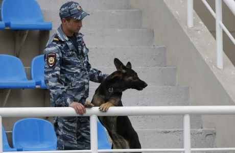 Russian police officer, with a sniffing dog, secures an area at a stadium prior to Russian Athletics Cup, at Zhukovsky, outside Moscow, Russia, Thursday, July 21, 2016. Russia lost its appeal Thursday against the Olympic ban on its track and field athletes, a decision which could add pressure on the IOC to exclude the country entirely from next month's games in Rio de Janeiro. (AP Photo/Alexander Zemlianichenko)
