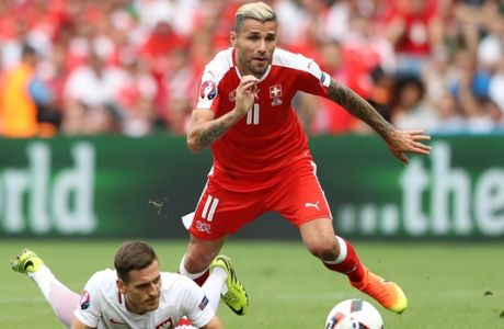 Switzerland's Valon Behrami, right, gets the ball past Poland's Arkadiusz Milikduring the Euro 2016 round of 16 soccer match between Switzerland and Poland, at the Geoffroy Guichard stadium in Saint-Etienne, France, Saturday, June 25, 2016. (AP Photo/Laurent Cipriani)