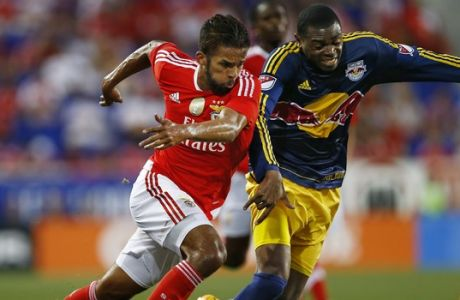 SL Benfica midfielder Mehdi Carcela-Gonzalez, left, battles New York Red Bulls defender Anthony Wallace for the ball during the first half of a soccer match in the International Champions Cup in Harrison N.J., Sunday, July 26, 2015. The Red Bulls defeated Benfica 2-1. (AP Photo/Rich Schultz)