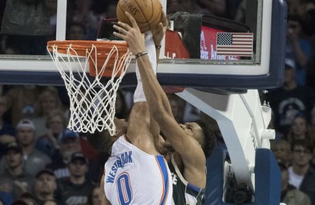Milwaukee Bucks forward Giannis Antetokounmpo (34) shoots the winning goal as Oklahoma City Thunder guard Russell Westbrook (0) applies pressure during the second half of an NBA basketball game in Oklahoma City, Friday, Dec.29, 2017. The Bucks defeated the Thunder 97-95. (AP Photo/J Pat Carter)