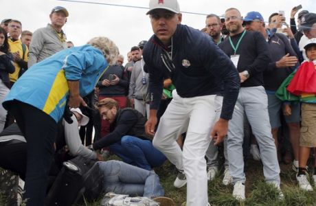 Brooks Koepka of the US gives a dedicated golf glove to spectator he wounded when his ball hit her on the 6th hole during his fourball match on the opening day of the 42nd Ryder Cup at Le Golf National in Saint-Quentin-en-Yvelines, outside Paris, France, Friday, Sept. 28, 2018. (AP Photo/Francois Mori)