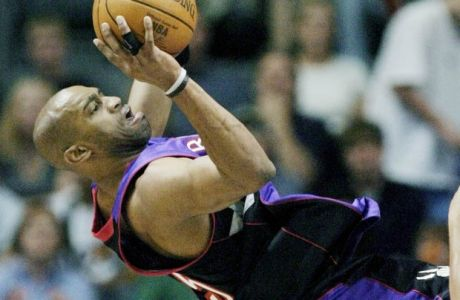 Toronto Raptors' Vince Carter, left, takes an off-balanced shot against Detroit Pistons' Tayshaun Prince (22) in the first half of their pre-season game at Van Andel Arena Sunday, Oct. 12, 2003, in Grand Rapids, Mich. (AP Photo/Duane Burleson)
