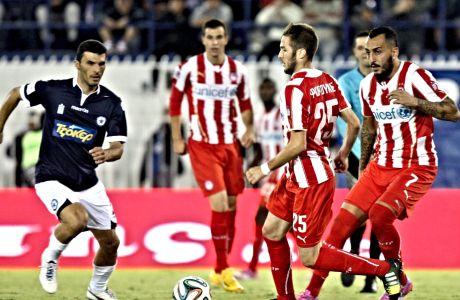 O Κώστας Φορτούνης με την μπάλα στα πόδια, ενώ παρακολουθούν οι Κώστας Μήτρογλου-Λούκα Μιλιβόγιεβιτς, κατά τη διάρκεια του Ατρόμητος-Ολυμπιακος 1-0 (27 Σεπτεμβρίου 2014).