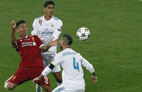 Liverpool's Roberto Firmino, left, challenges for the ball with Real Madrid's Sergio Ramos, right, and Raphael Varane during the Champions League Final soccer match between Real Madrid and Liverpool at the Olimpiyskiy Stadium in Kiev, Ukraine, Saturday, May 26, 2018. (AP Photo/Darko Vojinovic)