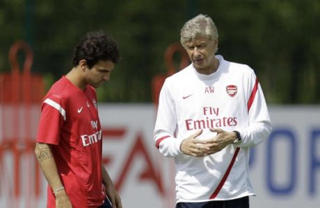 Arsenal's Cesc Fabregas, left, talks to his French manager Arsene Wenger at the start of a training session at the club's facilities in London Colney, England, Friday, Aug. 5, 2011.  The new English Premier League season starts on August 13 and it has been another offseason of unsettling speculation for Arsenal about whether captain Cesc Fabregas will return to Barcelona.  (AP Photo/Matt Dunham)