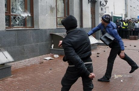 Ultra-right activists throw stones at the windows of a Russian government's center of culture and science, during at protest in central Kiev, Ukraine, Sunday, Feb. 18, 2018.  (AP Photo/Efrem Lukatsky)