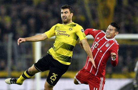 Dortmund's Sokratis, left, and Bayern's James, right, challenge for the ball during the German Bundesliga soccer match between Borussia Dortmund and FC Bayern Munich in Dortmund, Germany, Saturday, Nov. 4, 2017. (AP Photo/Martin Meissner)