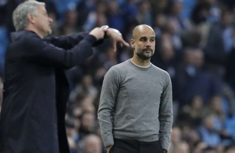 Manchester United manager Jose Mourinho gestures next to Manchester City coach Pep Guardiola, right, during the English Premier League soccer match between Manchester City and Manchester United at the Etihad Stadium in Manchester, England, Saturday April 7, 2018. (AP Photo/Matt Dunham)