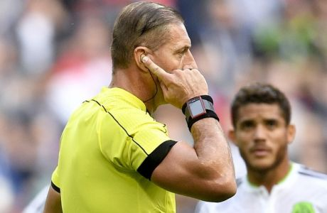 Argentine referee Nestor Pitana talks with VAR officials during the Confederations Cup, Group A soccer match between Portugal and Mexico, at the Kazan Arena, Russia, Sunday, June 18, 2017. (AP Photo/Martin Meissner)