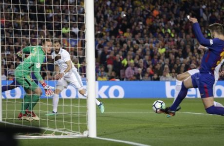 Real Madrid's Cristiano Ronaldo, hidden in white, right, scores his side's first goal as Barcelona's Gerard Pique, right, and Barcelona goalkeeper Marc-Andre ter Stegen tries and stop the shot during a Spanish La Liga soccer match between Barcelona and Real Madrid, dubbed 'El Clasico', at the Camp Nou stadium in Barcelona, Spain, Sunday, May 6, 2018. (AP Photo/Emilio Morenatti)