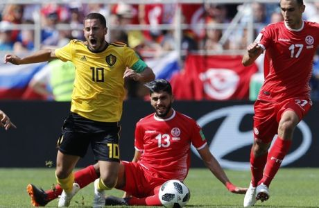 Belgium's Eden Hazard, center, falls on the pitch, as Tunisia's Ferjani Sassi, center right, challenges for the ball during the group G match between Belgium and Tunisia at the 2018 soccer World Cup in the Spartak Stadium in Moscow, Russia, Saturday, June 23, 2018. (AP Photo/Hassan Ammar)