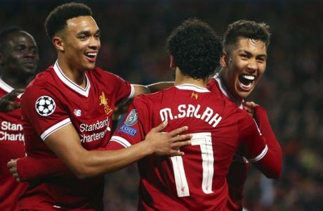 Liverpool's Roberto Firmino, right, celebrates after scoring his side's fourth goal during the Champions League semifinal, first leg, soccer match between Liverpool and AS Roma at Anfield Stadium, Liverpool, England, Tuesday, April 24, 2018. (AP Photo/Dave Thompson)