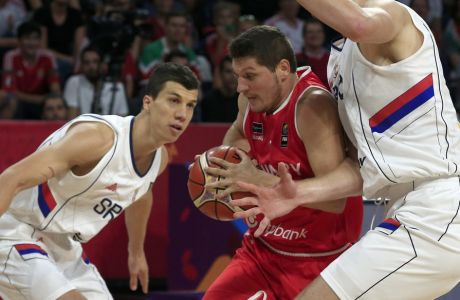 Hungary's Krisztian Wittmann, center, drives to the basket as Serbia's Ognjen Kuzmic, right, tries to block him during their Eurobasket European Basketball Championship round of 16 match in Istanbul, Sunday, Sept. 10. 2017. (AP Photo/Lefteris Pitarakis)