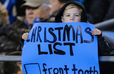 A Carolina Panthers' fan displays his Christmas list during the first half of an NFL football game against the Miami Dolphins in Charlotte, N.C., Monday, Nov. 13, 2017. The Panthers won 45-21. (AP Photo/Bob Leverone)