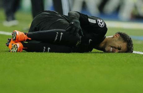 PSG's Neymar lies on the pitch after being fouled during the Champions League soccer match, round of 16, 1st leg between Real Madrid and Paris Saint Germain at the Santiago Bernabeu stadium in Madrid, Spain, Wednesday, Feb. 14, 2018. (AP Photo/Paul White)