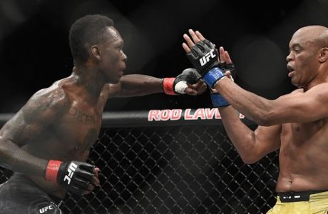 Nigeria's Israel Adesanya, left, and Brazil's Anderson Silva fight during their middleweight bout at the UFC 234 event in Melbourne, Australia, Sunday, Feb. 10, 2019. (AP Photo/Andy Brownbill)