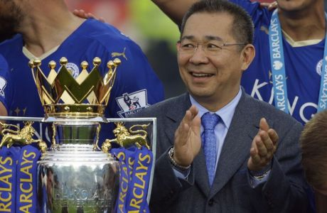 Vichai Srivaddhanaprabha applauds beside the trophy as Leicester City celebrate becoming the English Premier League soccer champions at King Power stadium in Leicester, England, Saturday, May 7, 2016.(AP Photo/Matt Dunham)