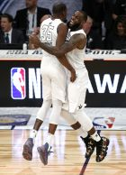 Team LeBron's Kevin Durant, left, of the Golden State Warriors, celebrates with Team LeBron's LeBron James, of the Cleveland Cavaliers, during the second half of an NBA All-Star basketball game, Sunday, Feb. 18, 2018, in Los Angeles. Team LeBron won, 148-145. (AP Photo/Alex Gallardo)