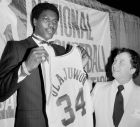 O Χακίμ Ολάζουον ήταν ο πρώτος, γεννημένος στην Αφρική, NBAer. Επελέγη στο 1984 NBA draft από τους Ρόκετς, στο Νο1. Είχε φοιτήσει/παίξει στο University of Houston, όπου πήγε γιατί ένας φίλος του κόουτς Γκάι Λιούις του είχε μιλήσει για αυτόν. Είχε ξεκινήσει το μπάσκετ σε ηλικία 17 χρόνων, στο Λάγος. Έως τότε έπαιζε ως τερματοφύλακας, σε ποδοσφαιρική ομάδα. (AP Photo/Marty Lederhandler)