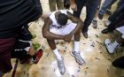 Montana guard Will cherry (5) sits on the court as the team celebrates defeating Weber State 67-64 in the Big Sky Conference tournament championship NCAA college basketball game in Missoula, Mont., on Saturday, March 16, 2013. (AP Photo/ Michael Albans)