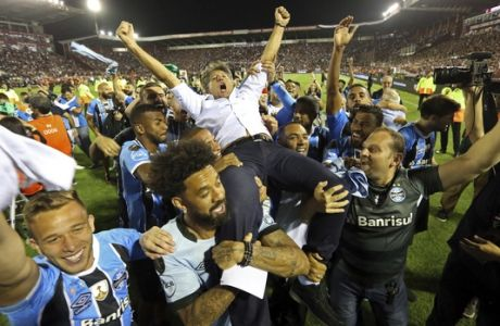 In this Wednesday, Nov. 29, 2017 photo, Brazil's Gremio soccer players carry their coach Renato Gaucho after clenching the Copa Libertadores championship following their victory over Argentina's Lanus in Buenos Aires, Argentina. (AP Photo/Esteban Felix)