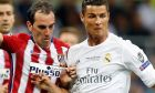 Atletico's Diego Godin, left, challenges Real Madrid's Cristiano Ronaldo during the Champions League final soccer match between Real Madrid and Atletico Madrid at the San Siro stadium in Milan, Italy, Saturday, May 28, 2016.  (AP Photo/Manu Fernandez)
