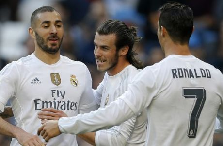Real Madrid's Karim Benzema, left, celebrates with teammates Cristiano Ronaldo, right, and Gareth Bale after scoring their side's third goal against Getafe during the Spanish La Liga soccer match between Real Madrid and Getafe at the Santiago Bernabeu stadium in Madrid, Saturday, Dec. 5, 2015. Benzema scored twice and Ronaldo and Bale scored once each in Real Madrid's 4-1 victory. (AP Photo/Francisco Seco)