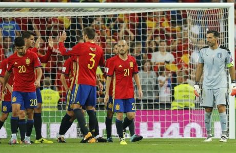 Italy goalkeeper Gianluigi Buffon , right, watches as Spain players celebrate after scoring their third goal during the World Cup Group G qualifying soccer match between Spain and Italy at the Santiago Bernabeu Stadium in Madrid, Saturday Sept. 2, 2017. (AP Photo/Paul White)