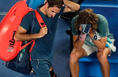 Switzerland's Roger Federer, left, leaves Rod Laver Arena after losing his fourth round match to Greece's Stefanos Tsitsipas at the Australian Open tennis championships in Melbourne, Australia, Sunday, Jan. 20, 2019. (AP Photo/Kin Cheung)