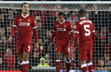 Liverpool's Joel Matip, centre, appears dejected after scoring an own-goal for West Bromwich Albion's third goal during the English FA Cup, fourth round soccer match between Liverpool and West Bromwich Albion, at the Anfield stadium, Liverpool, England, Saturday Jan. 27, 2018. (Peter Byrne/PA via AP)