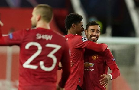 Manchester United's Marcus Rashford, center, celebrates with Manchester United's Bruno Fernandes after scoring his side's second goal during the Champions League group H soccer match between Manchester United and RB Leipzig, at the Old Trafford stadium in Manchester, England, Wednesday, Oct. 28, 2020. (AP Photo/Dave Thompson)