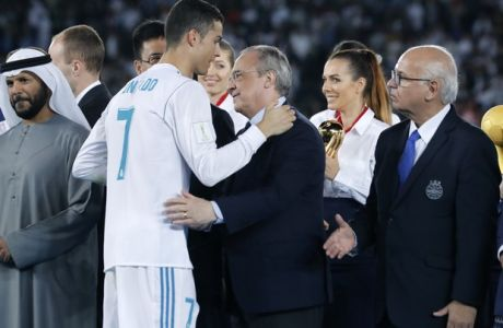 Real Madrid's Cristiano Ronaldo greets Real Madrid President Florentino Perez, center, and Gremio President Romildo Bolzan Jr., right, after winning the Club World Cup final soccer match between Real Madrid and Gremio at Zayed Sports City stadium in Abu Dhabi, United Arab Emirates, Saturday, Dec. 16, 2017. (AP Photo/Hassan Ammar)