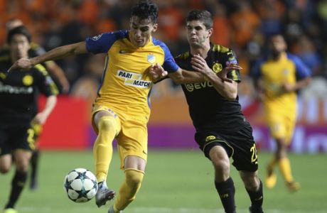 APOEL Nicosia's Praksitelis Vouros, left, and Dortmund's Christian Pulisic challenge for the ball during the Champions League Group H soccer match between APOEL Nicosia and Borussia Dortmund at GSP stadium, in Nicosia, Cyprus, on Tuesday, Oct. 17, 2017. (AP Photo/Petros Karadjias)
