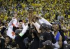 Golden State Warriors players, coaches and owners hold up the Larry O'Brien NBA Championship Trophy after Game 5 of basketball's NBA Finals between the Warriors and the Cleveland Cavaliers in Oakland, Calif., Monday, June 12, 2017. The Warriors won 129-120 to win the NBA championship. (AP Photo/Marcio Jose Sanchez)