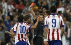 Referee Felix Brych shows a red card to Atletico's Arda Turan, left, during the second leg quarterfinal Champions League soccer match between Real Madrid and Atletico Madrid at Santiago Bernabeu stadium in Madrid, Spain, Wednesday, April 22, 2015. (AP Photo/Andres Kudacki)