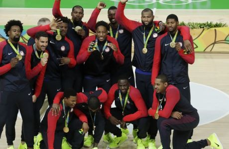 The United States' basketball team poses with their gold medals at the 2016 Summer Olympics in Rio de Janeiro, Brazil, Sunday, Aug. 21, 2016. (AP Photo/Charlie Neibergall)