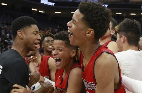 Crossroads forward Shareef O'Neal, right, hugs his younger brother, Shaqir, as they celebrate with teammates after defeating Alameda in the Division II boys high school championship game Friday, March 23, 2018, in Sacramento, Calif. The two O'Neals are the sons of NBA Hall of Fame center Shaquille O'Neal. (AP Photo/Rich Pedroncelli)