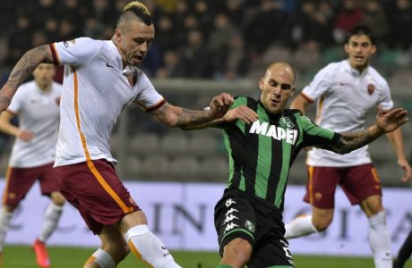 In this Tuesday, Feb. 2, 2016 file photo, Sassuolo's Paolo Cannavaro, right, vies for the ball with Roma's Radja Nainggolan, during a Serie A soccer match in Reggio Emilia, Italy. Paolo Cannavaro will quit soccer after this weekend and join his brother on the technical staff at Chinese club Guangzhou Evergrande. (AP Photo/Marco Vasini)