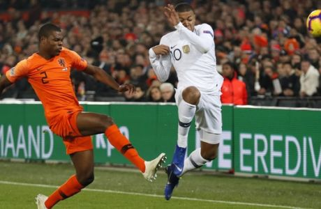 Netherlands' Denzel Dumfries clears before France's Kylian Mbappe, right, can accept a pass during the international friendly soccer match between The Netherlands and France at De Kuip stadium in Rotterdam, Netherlands, Friday, Nov. 16, 2018. (AP Photo/Peter Dejong)