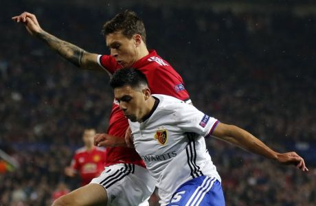 Manchester United's Victor Lindelof is challenged by Basel's Blas Riveros, right, during the Champions League group A soccer match between Manchester United and Basel, at the Old Trafford stadium in Manchester, Tuesday, Sept. 12, 2017. (AP Photo/Frank Augstein)