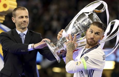 UEFA President Aleksander Ceferin, left, hands the trophy to Real Madrid's Sergio Ramos after the Champions League Final soccer match between Juventus and Real Madrid at the Millennium Stadium in Cardiff, Wales, Saturday, June 3, 2017. (Nick Potts/PA via AP)