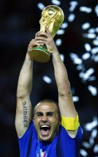 ** FILE ** Italian team captain Fabio Cannavaro holds aloft the World Cup trophy after the final of the soccer World Cup between Italy and France in the Olympic Stadium in Berlin, in this Sunday, July 9, 2006 file photo. Cannavaro has added the World Soccer magazine player of the year award to his European prize. Three weeks after receiving the Golden Ball, with the most votes polled by France Football magazine, the Real Madrid defender was a runaway winner Friday, Dec. 15, 2006 of the World Soccer poll of its readers. (AP Photo/Jasper Juinen/Files)  ** MOBILE/PDA USAGE OUT **