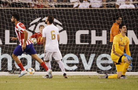 Atletico Madrid's Diego Costa, left, celebrates after scoring his third goal of the game on a penalty kick as Real Madrid's goalkeeper Thibaut Courtois reacts during the first half of a soccer match Friday,July 26, 2019, in East Rutherford, N.J. (AP Photo/Frank Franklin II)
