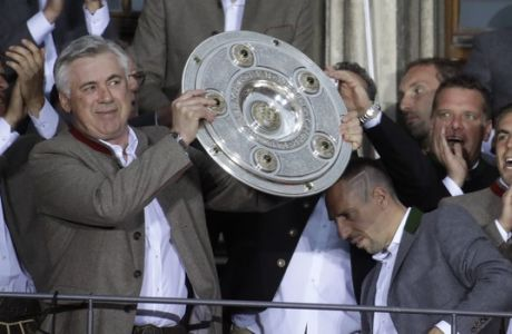 FILE - In this May 20, 2017 file photo Bayern's head coach Carlo Ancelotti lifts the trophy as his team celebrate on the balcony of the town hall at Marienplatz square after winning the 27th Bundesliga title at the German first division Bundesliga soccer match between FC Bayern Munich and SC Freiburg at the Allianz Arena stadium in Munich, Germany. Bayern Munich fired Carlo Ancelotti as coach on Thursday after the German team's heaviest Champions League group-stage defeat.   (AP Photo/Matthias Schrader, file)
