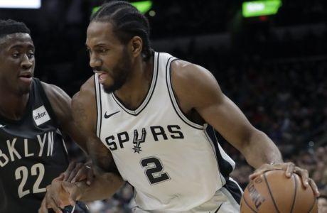 San Antonio Spurs forward Kawhi Leonard (2) drives around Brooklyn Nets guard Caris LeVert (22) during the first half of an NBA basketball game, Tuesday, Dec. 26, 2017, in San Antonio. (AP Photo/Eric Gay)